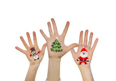 Le mani dei bambini che si alzano su con i simboli dipinti di Natale: Santa Claus, albero di Natale, uomo della neve Immagini Stock