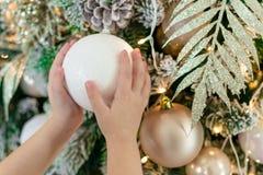 Le mani dei bambini che tengono una grande palla di natale bianco decora l'albero di Natale Nuovo anno 2019 immagini stock libere da diritti