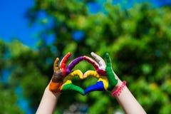 Le mani dei bambini dipinte nei colori luminosi fanno una forma del cuore sul fondo della natura dell'estate Fotografie Stock