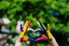 Le mani dei bambini dipinte nei colori luminosi fanno una forma del cuore sul fondo della natura dell'estate immagine stock