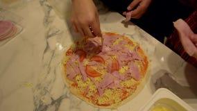 Le mani dei bambini producono la pizza, aggiungono il prosciutto sul dolce stock footage