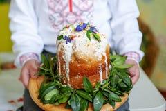 Le mani dei bambini tengono il dolce decorato di Pasqua, primo piano fotografia stock