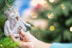 Le mani dei bambini tengono la decorazione all'albero di Natale su cui i giocattoli del nuovo anno stanno appendendo Concetto di  immagine stock