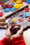 Le mani dei bambini tengono un uovo di Pasqua decorato Cottura dei biscotti tradizionali di Pasqua Uova di Pasqua Concetto dell'a immagini stock libere da diritti