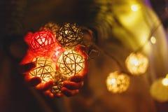 Le mani dei bambini tengono una ghirlanda della palla per il Natale o il nuovo anno a casa sul fondo delle luci Celebrazione di N fotografie stock