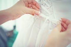 Le mani dei bridemaids stanno legando l'arco sul vestito da sposa alla moda della sposa Nessun fronte fotografie stock