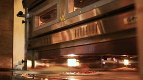 Le mani dei cuochi unici aspettano la pizza che ottiene dal forno fine video d archivio