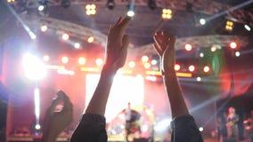 Le mani dei fan applaudono sull'evento di notte in illuminazione luminosa stock footage