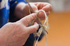 Le mani dei ferri da maglia anziani di una donna, facenti cucito fotografie stock