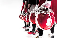 Le mani dei giocatori di football americano con i caschi su fondo bianco fotografia stock libera da diritti
