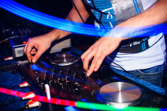 Le mani dei regolatori torcono la musica del DJ sull'attrezzatura del DJ in night-club Fotografia Stock Libera da Diritti