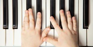 Le mani del bambino che giocano il piano fotografia stock libera da diritti