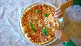 Le mani del bambino che prendono una fetta di pizza da un piatto bianco in ristorante, caffè Primo piano Il ragazzino o la ragazz video d archivio