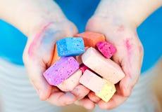 Le mani del bambino che tengono i pezzi colorati del gesso Fotografia Stock