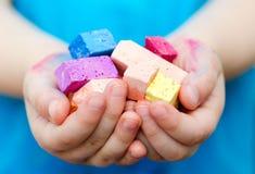 Le mani del bambino che tengono i pezzi colorati del gesso Immagini Stock Libere da Diritti