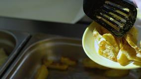Le mani del bambino hanno messo Fried Potatoes sul piatto stock footage