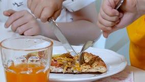Le mani del bambino hanno tagliato una fetta di pizza stock footage