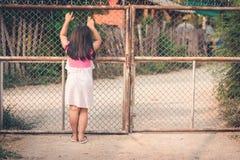 Le mani del bambino su un recinto della maglia del nastro metallico immagine stock libera da diritti