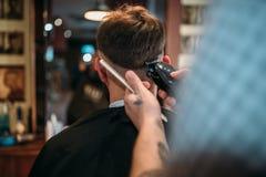 Le mani del barbiere fa l'acconciatura del cliente dal tagliatore Fotografia Stock