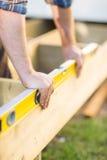 Le mani del carpentiere che controllano a livello del legno Fotografia Stock Libera da Diritti