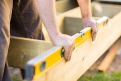 Le mani del carpentiere che controllano a livello del legno al sito Immagini Stock Libere da Diritti