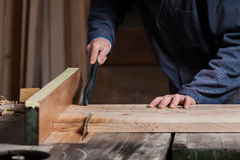 Le mani del carpentiere che tagliano il bordo di legno con la Tabella hanno visto Fotografia Stock