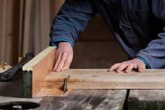 Le mani del carpentiere che tagliano il bordo di legno con la Tabella hanno visto Immagini Stock