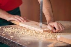 Le mani del carpentiere che tagliano legno con la sega a nastro Fotografia Stock Libera da Diritti