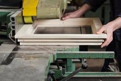 Le mani del carpentiere che tagliano struttura della finestra di legno Immagini Stock Libere da Diritti