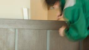 Le mani del carpentiere del primo piano con il doorlock durante la serratura trasformano l'installazione nel timelapse di legno d video d archivio