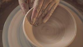 Le mani del ceramista tengono una ciotola dell'argilla che gira su una ruota del ` s del vasaio archivi video