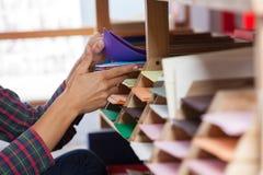 Le mani del cliente che selezionano la cartolina d'auguri a partire Fotografia Stock