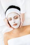 Le mani del cosmetologo applicano la crema al fronte della donna Fotografia Stock