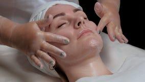 Le mani del cosmetologo massaggiano il fronte ed applicano la crema d'idratazione alle guance femminili del cliente Ritratto di u fotografie stock