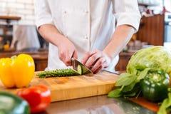 Le mani del cuoco unico cucinano le verdure di taglio ed insalata di fabbricazione Immagine Stock