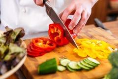 Le mani del cuoco unico cucinano le verdure di taglio sulla tavola di legno Fotografia Stock