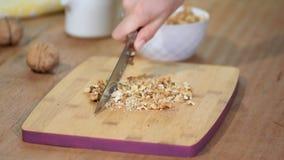 Le mani del cuoco unico femminile che tagliano le noci a pezzi sul tagliere di legno archivi video