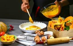 Le mani del cuoco unico hanno messo la pasta in una muffa, cuoco per cuocere la torta di zucca americana con cannella e formaggio fotografia stock libera da diritti