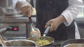 Le mani del cuoco unico professionista mescola gli spaghetti su una pentola Il cuoco lavora in una cucina moderna con i lotti deg Fotografia Stock Libera da Diritti