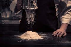 Le mani del cuoco unico stanno cadendo la farina sopra una tavola di legno fotografia stock