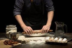 Le mani del cuoco unico stanno rotolando una pasta per produrre la pizza immagine stock libera da diritti