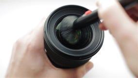 Le mani del fotografo o del videographer libera il vetro anteriore di una lente da polvere e dalla sporcizia con l'aiuto di un pr archivi video
