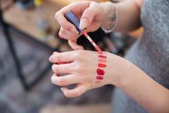 Le mani del labbro di prova del truccatore della donna lucidano a disposizione Fotografie Stock