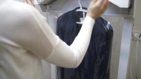 Le mani del lavoratore che mettono imballaggio sul vestito pulito archivi video