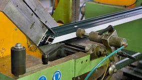 Le mani del lavoratore hanno tagliato il profilo di alluminio con la sega circolare sul movimento lento della fabbrica stock footage