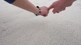 Le mani del maschio e della donna dipingono il simbolo del cuore sulla sabbia della spiaggia Spiaggia di Pensacola, Florida video d archivio