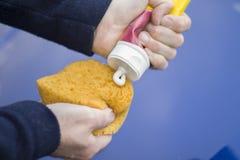 Le mani del meccanico di automobile applicano una pasta di lucidatura sulla spugna Fotografia Stock Libera da Diritti