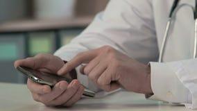 Le mani del medico che fanno scorrere gli archivi, testo di battitura a macchina sullo smartphone, consulto medico stock footage