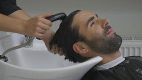 Le mani del parrucchiere versano l'acqua ai capelli del ` s del cliente Il cliente lava i capelli dopo il taglio nel parrucchiere video d archivio