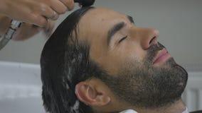 Le mani del parrucchiere versano l'acqua ai capelli del ` s del cliente Il cliente lava i capelli dopo il taglio nel parrucchiere stock footage